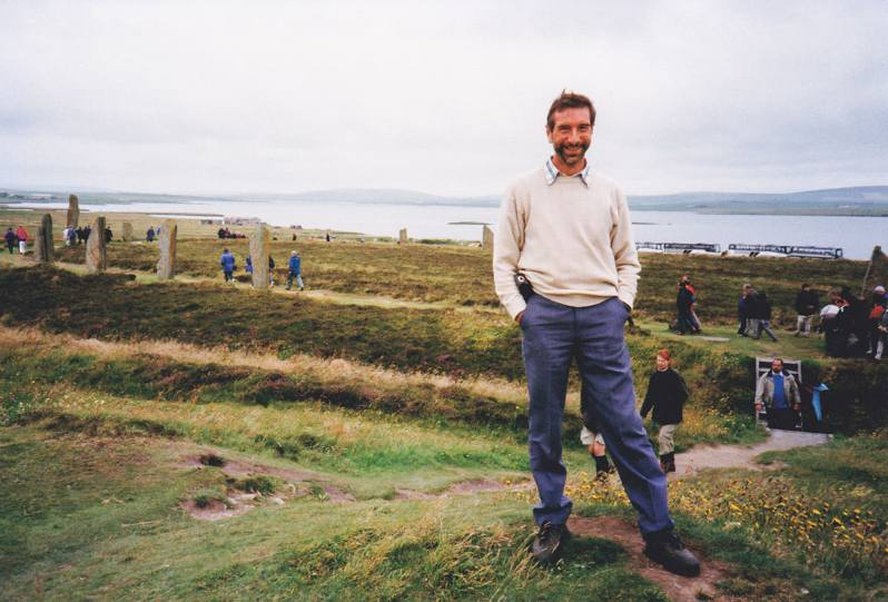 A man smiling with his hands in pockets, standing on a grassy knoll with a stone circle, people and a lake in the background