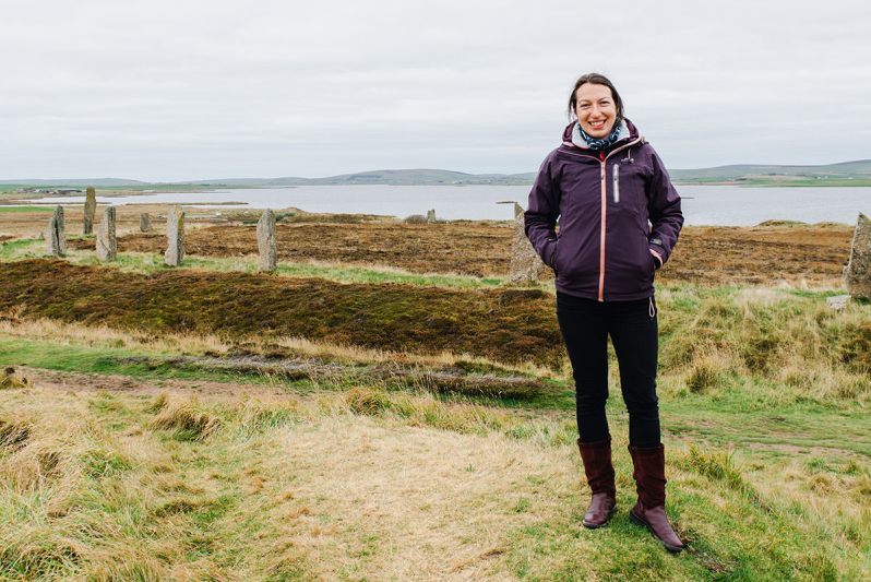 A woman smiling with hands in her pockets standing on a grassy knoll in front of a stone circle with a loch in the background