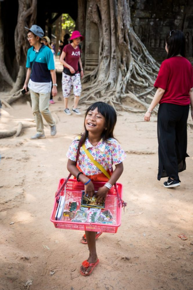 Little girl selling things at Ta Som for an Angkor Wat temple guide