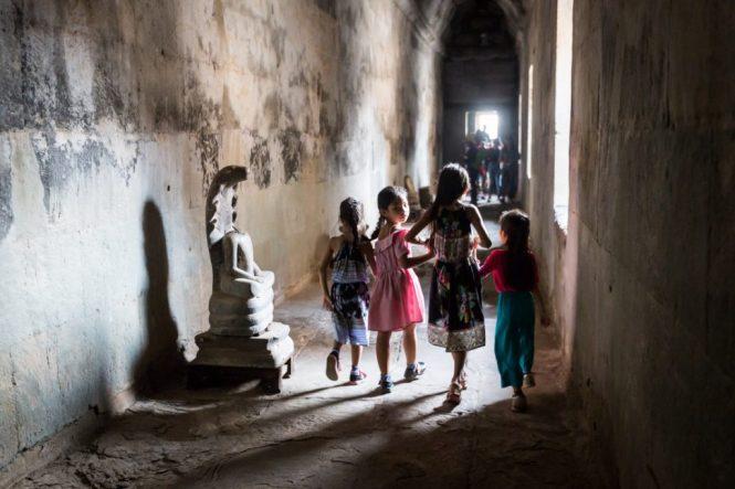 Girls walking down a hallway at Angkor Wat for an article on Angkor Wat travel tips