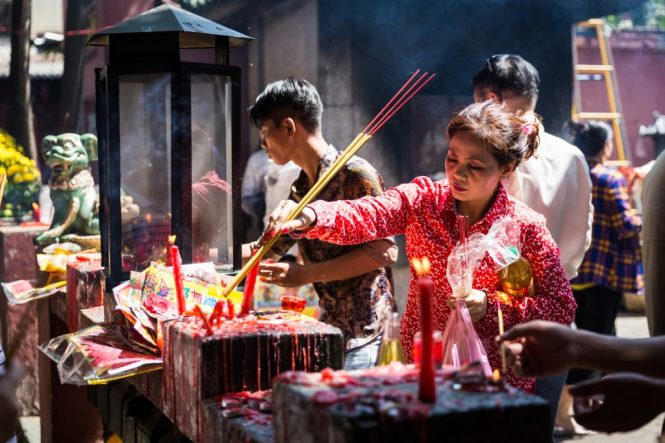 Woman lighting incense at the Ba Thien Hau temple for article on Ho Chi Minh City street photos