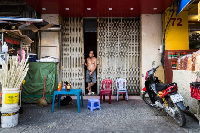 Shirtless man in doorway for article on Ho Chi Minh City street photos