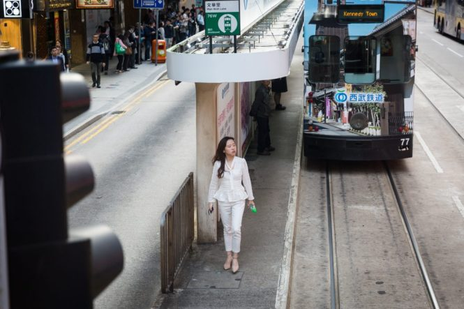 Woman at a ding ding station for a Hong Kong street photography series called the view from the ding ding