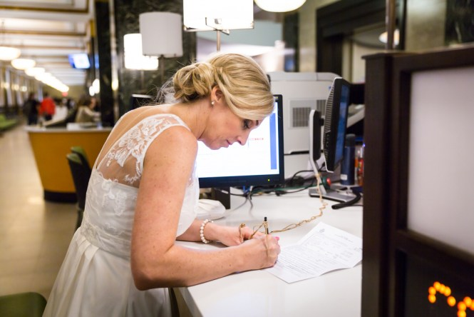 Couple signing paperwork for their NYC City Hall elopement