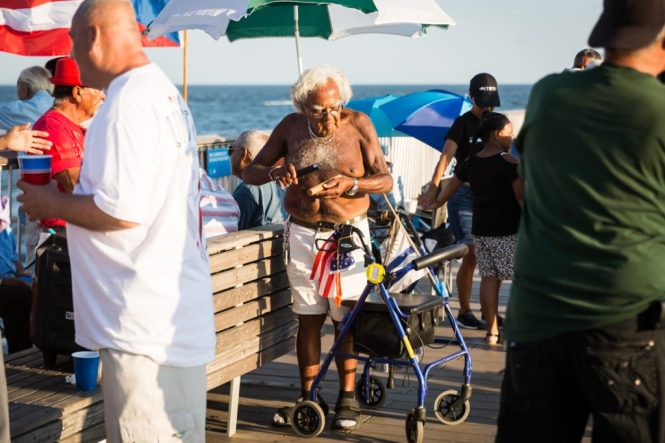 Old man with walker playing music on the Coney Island pier