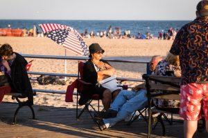 Woman wearing a hat on the Coney Island boardwalk