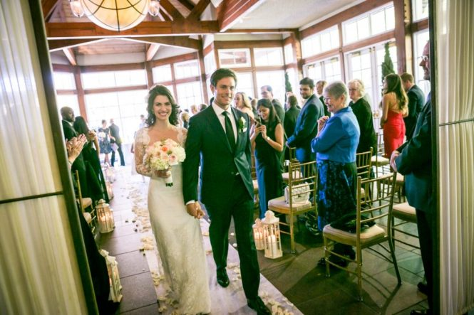 Bride and groom walking down aisle for an article on wedding officiant tips