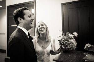 Bride and groom laughing for an article on How to Get Married at City Hall in Any NYC Borough