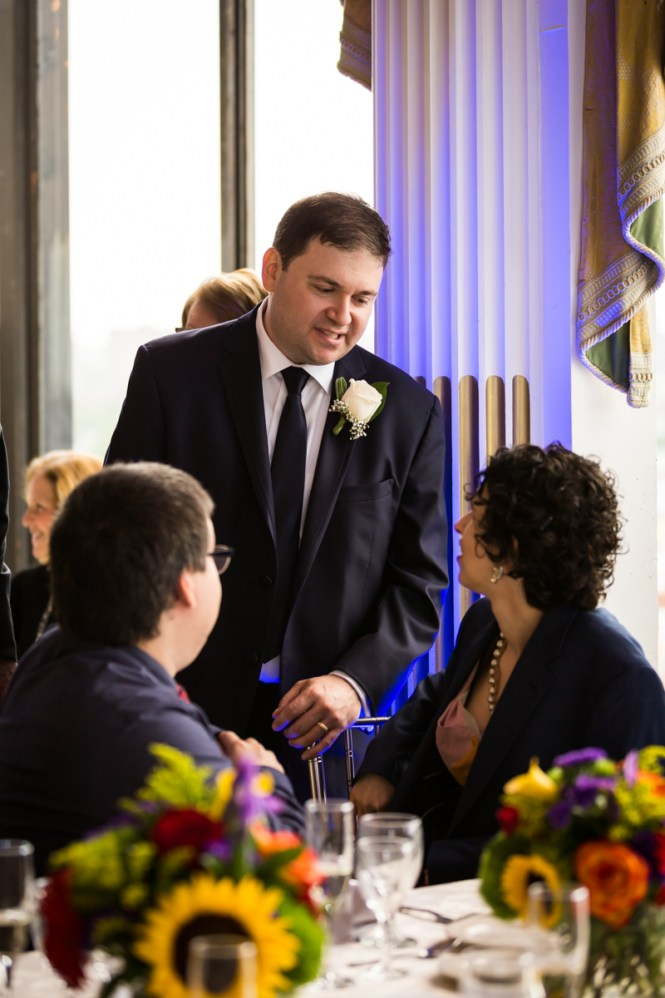 Groom talking with guests for article on a Terrace on the Park wedding