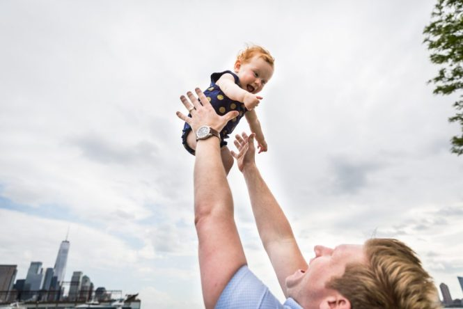 Dad throwing baby in the air in a Hudson River Park Family Portrait