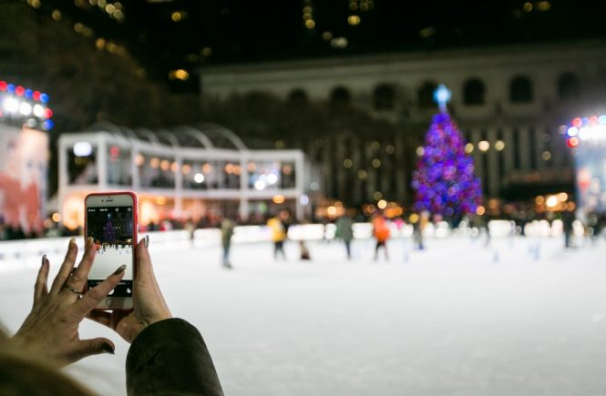 Woman taking cell phone photo of ice skating rink for an article on NYC holiday card location suggestions