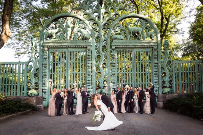 Bride and groom kissing in front of bridal party and Southern Boulevard gates for an article on Bronx Zoo wedding venue updates