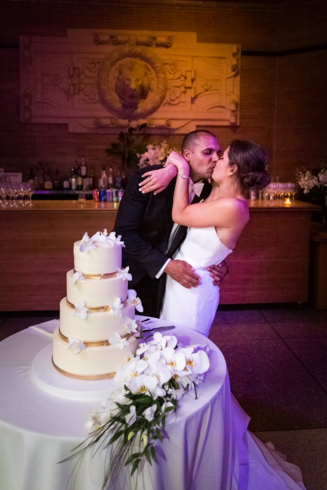 Bride and groom kissing by wedding cake for an article on Bronx Zoo wedding venue updates