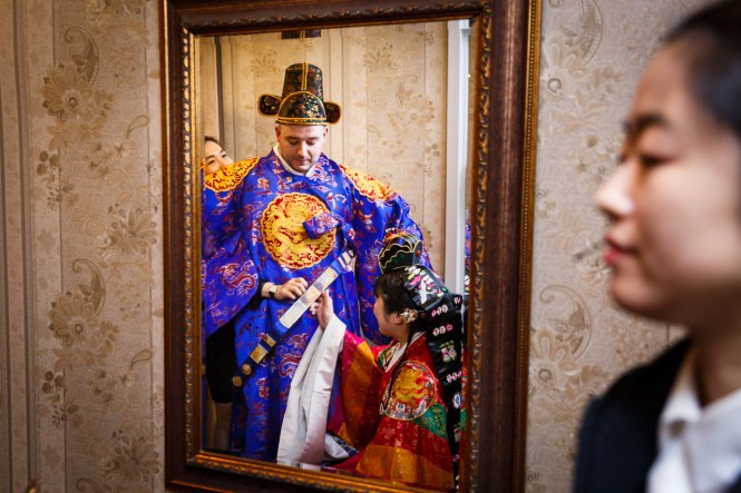 Bride and groom in mirror at traditional Korean pyebaek ceremony