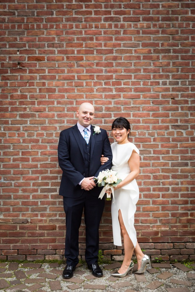 Bride and groom against brick wall