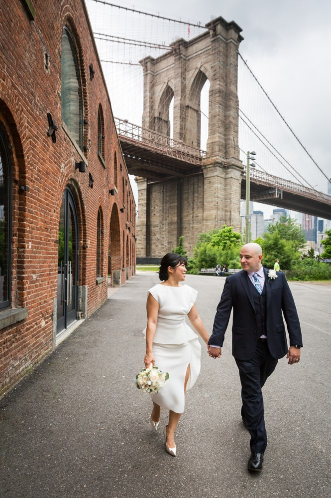 Bride and groom walking in front of Brooklyn Bridge