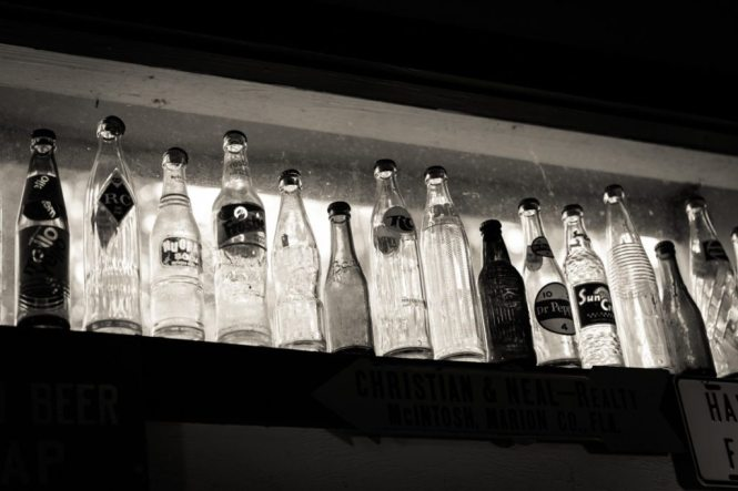 Antique soda bottles on display in a cafe