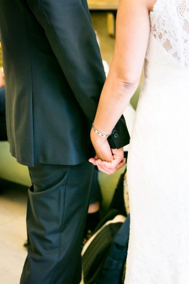 A couple holding hands, by NYC City Hall wedding photographer, Kelly Williams