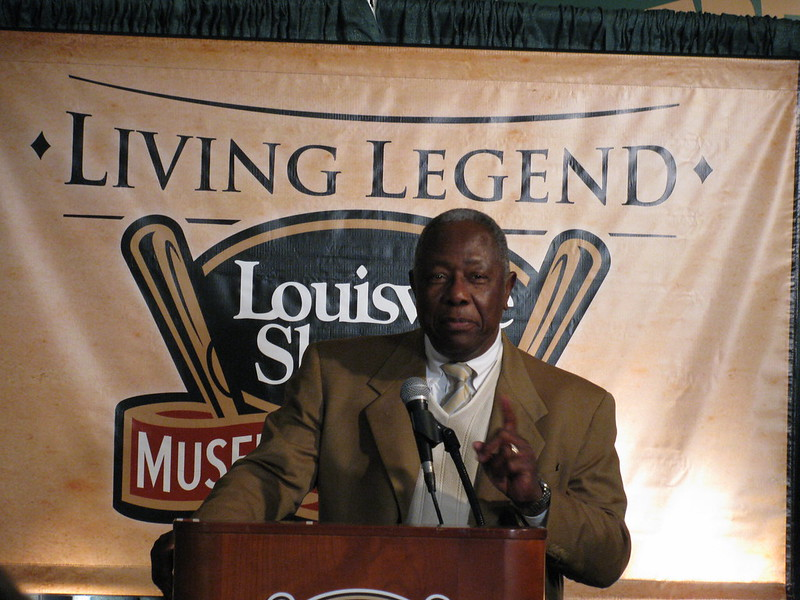 I picture of Hank Aaron in a suit and tie giving what appears to be a speech.