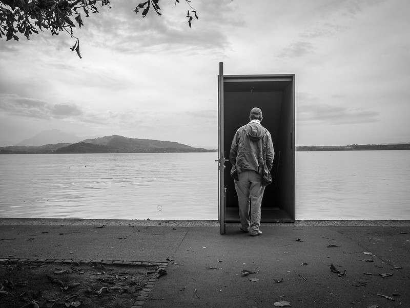 A person walks into an open door into a backdrop of a body of water.