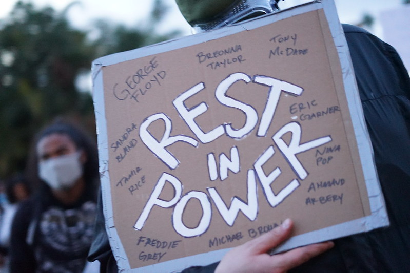 """A sign held up during protests in these days with """"Rest in Power"""" in white and the names of individuals in black that have died at the hands of police."""