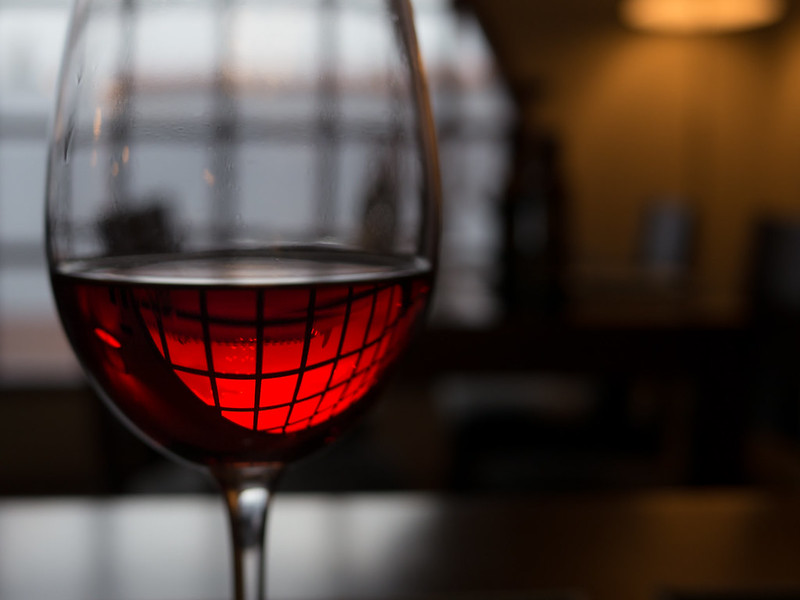 an image with a closeup with a glass of red wine, rest of background scene out of focus due to short depth of field.