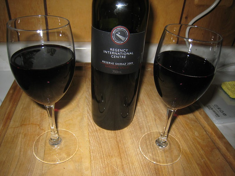 A bottle of red wine with two glasses served.