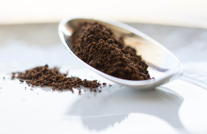 Ground coffee on a counter top and in a teaspoon.