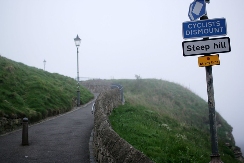 """A steep hill leading to a curve in the road. Sign visible stating """"Cyclists dismount"""" """"Steep hill"""""""