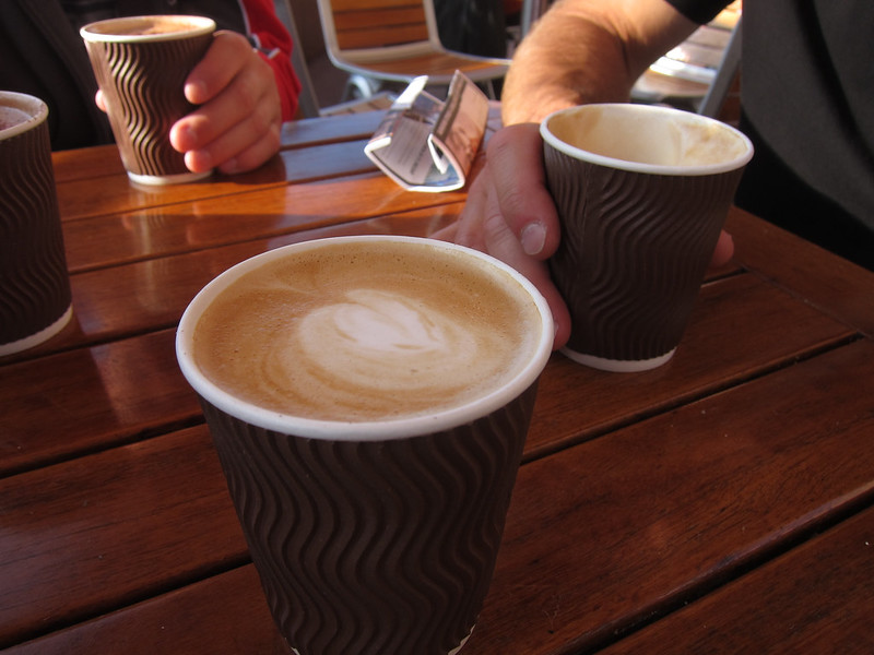 Picture of a table with hands on two of four coffees in take out cups.