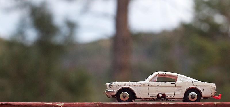 Toy car on a deck rail.