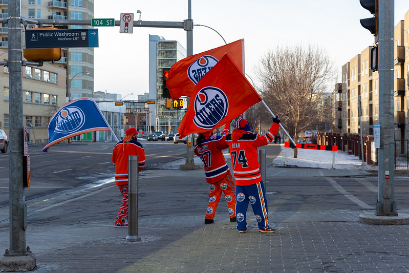 Three Edmonton Oilers fans near the rink in Oilers clothing and Oilers flags.