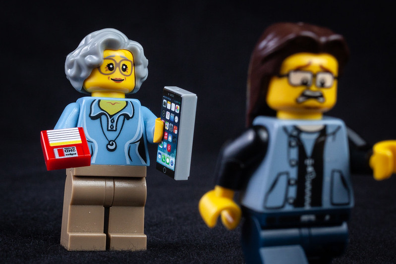 Lego figures, one older person with floppy disks and iPhone, younger person running away.