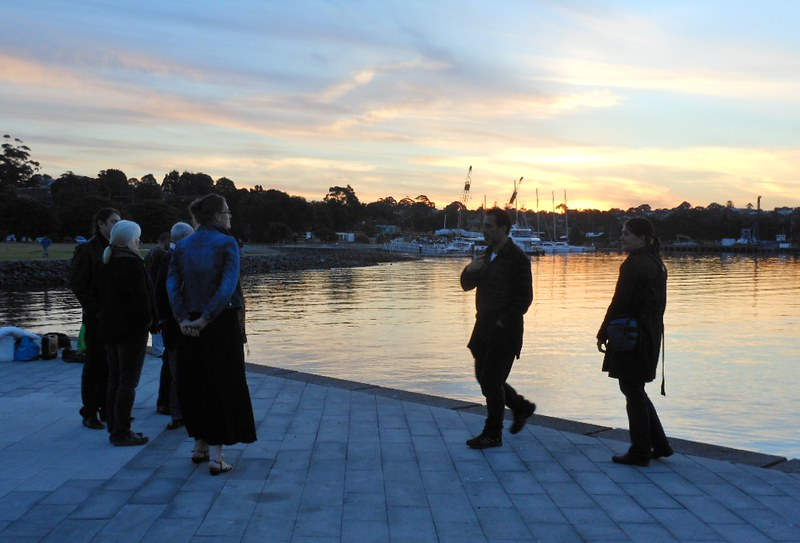 People reflecting during a sunset on a wharf in Sydney, NSW, Australia.