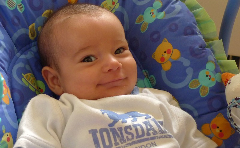 Close-up of a baby with a big smile on their face.