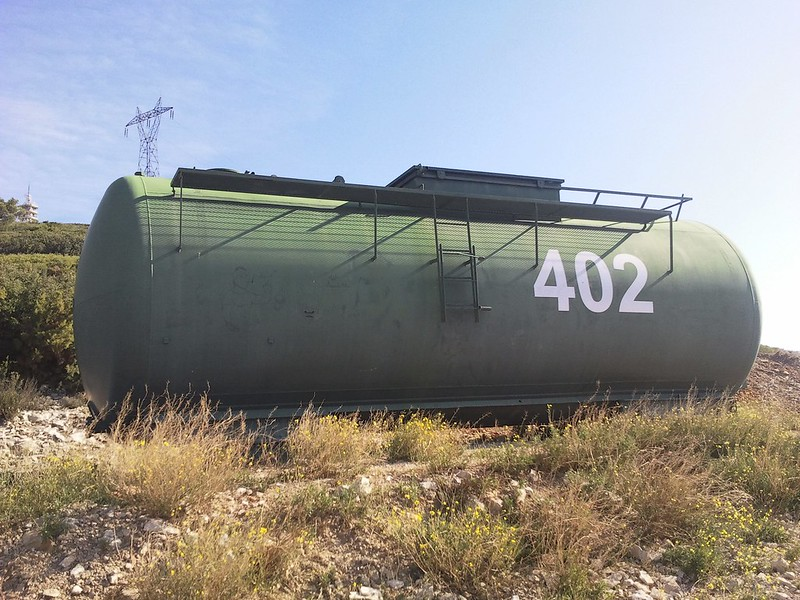 Image of a large green cistern tank with the number 402 somewhere in a field in the south of France.