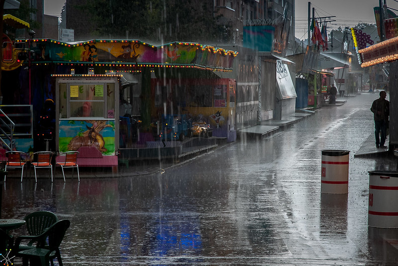 Rainy scene of a street corner with a lone person visible in a heavy rain.