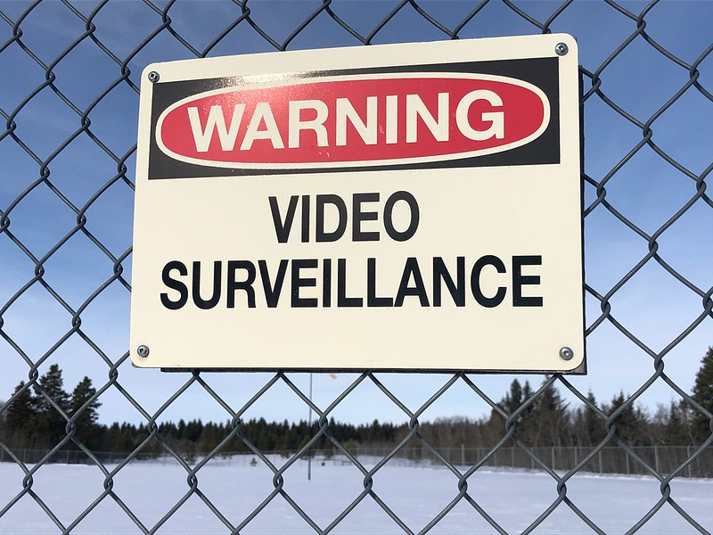 """Sign on chain link fence, """"Warning. Video Surveillance"""". Snowy field and trees in the background."""