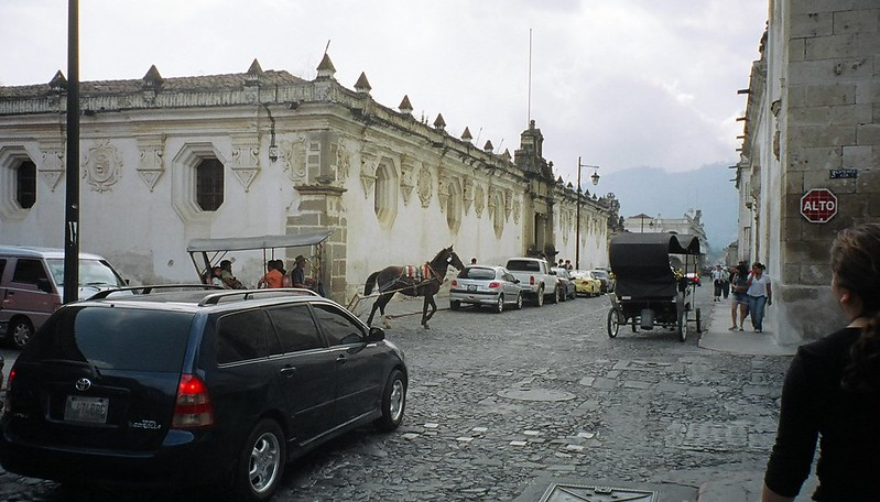 A street corner somewhere in Guatemala with cares and horse and buggies in view and some old large buildings.