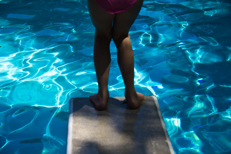 Close up of legs and pink bathing trunks about to jump from a standard height diving board into the blue of a swimming pool which takes up the rest of the image.