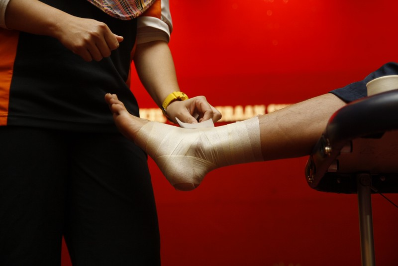 A physical therapist applying a bandage to the lower leg and ankle of a patient. Showing just the torso of the therapist and the leg of the patient, no visible faces.