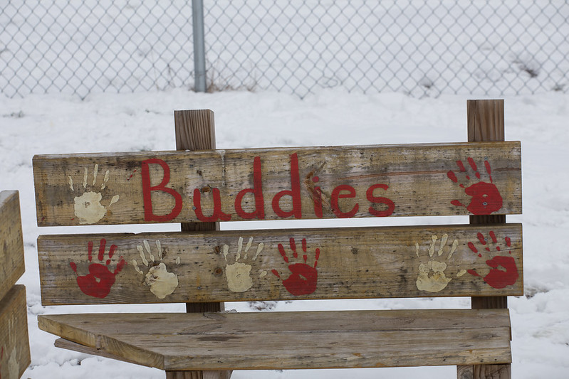 """Short wooden bench with snow and a fence in the background. Painted on the bench back is the word """"Buddies"""" in red with red and white hand prints on the back as well."""