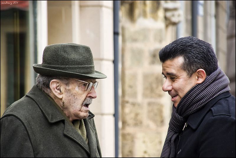 An elderly man in hat and glasses speaking with a middle-age man with a scarf. Close shot of both filling the fram from chest up.