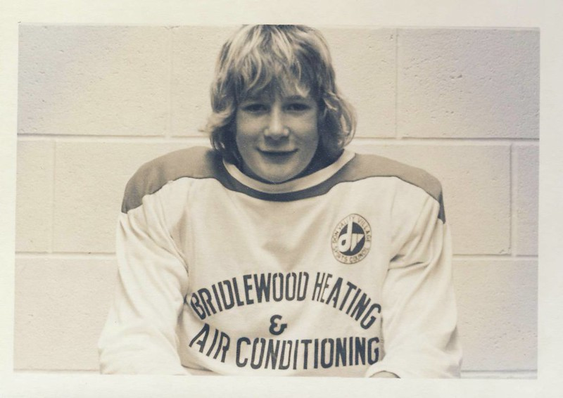 """Black and white photo of blonde haired teenager with long hair in a hockey jersey. Shot with the classic cinderblock dressing room wall behind the player, sitting and only jersey to head visible. Jersey reads """"Bridlewood Heating & Air Conditioning""""."""