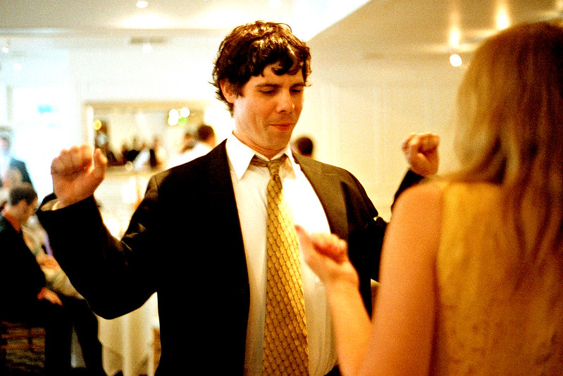 View of a couple dancing at a wedding. Women with her back to us; man in suit and tie with arms ready to pump up while busting out a dance move.