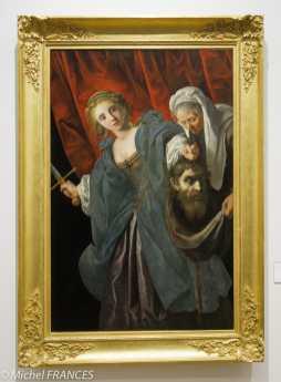 Anonyme - Judith et Holopherne - 17ème siècle - Dans l'Ancien Testament de la Bible, Judith, une jeune et pieuse veuve lulve, sauve la cité de Béthulie, assiégée par Holopherne, en séduisant celui-ci, puis en le décapitant dans son sommeil. Soucieux de peindre avec élégance ce sujet sanglant, l'artiste montre Judith après la décapitation. La jeune héroïne au visage angélique, blonde ici comme chez Le Caravage, met la tête du général dans le sac tendu par sa servante et s'apprête à fuir. L'influence de Gentileschi se ressent dans le coloris des tissus, le grand rideau rouge et la grâce de Judith. Plusieurs noms d'artistes florentins pour la grâce de Judith ou encore flamands pour le traitement des matières et du visage de la servante ont été avancés comme possibles auteurs de cette toile. Peut-être faut-il envisager un peintre français qui aurait su mêler ces différenles influences ?