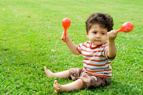 baby boy playing maracas outdoors