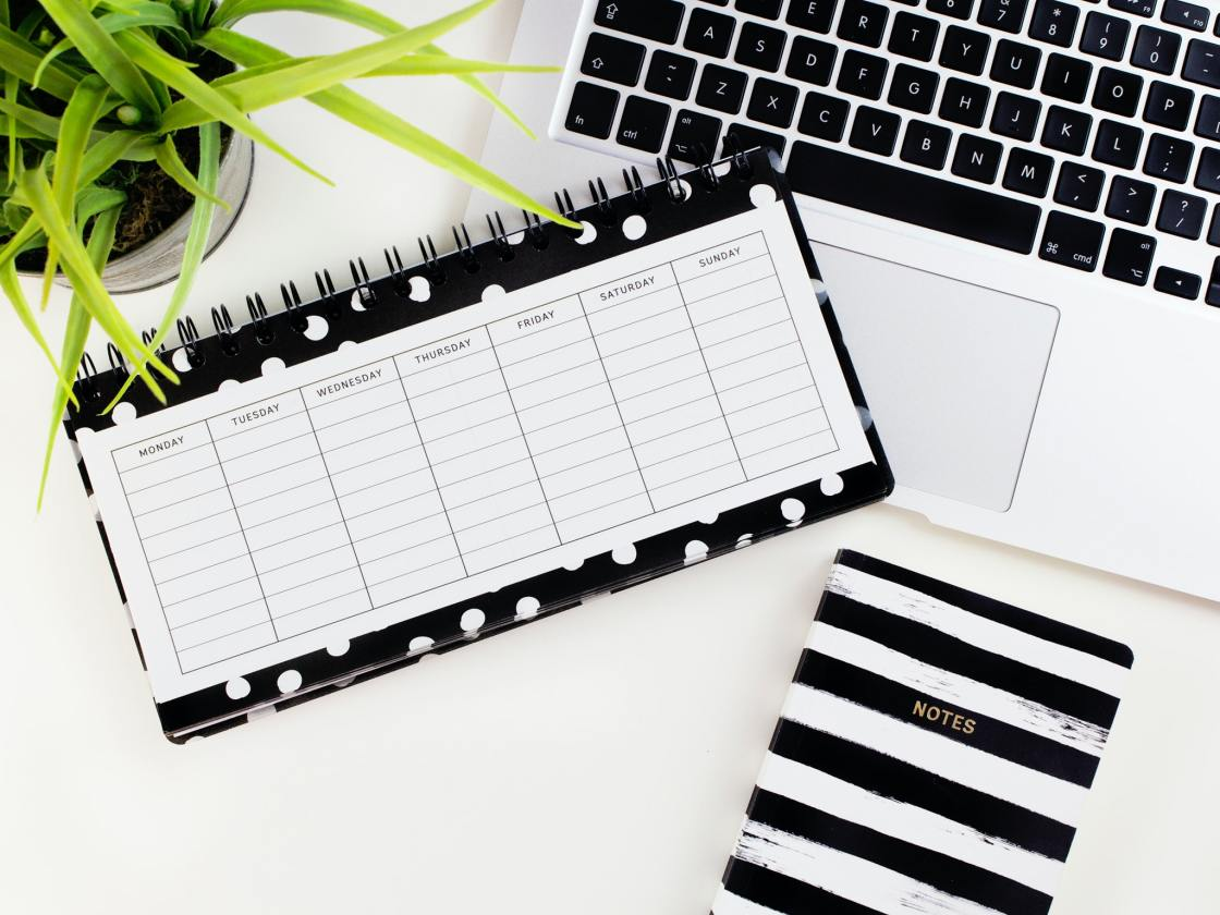 Weekly calendar planner on a desk next to a keyboard