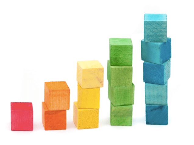 Colourful wooden building blocks stacked in increasing height using individual colours as an educational toy for young children