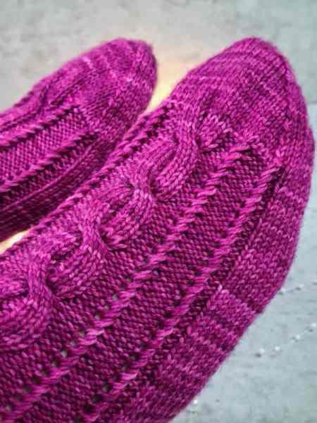 detailbild der socke mit strebe und gestrickten zopf der streben zum glück socke